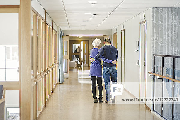 Rear view of senior woman walking with son in corridor at nursing home