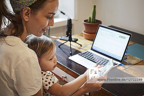 Podcaster showing mobile phone to daughter while using laptop at home