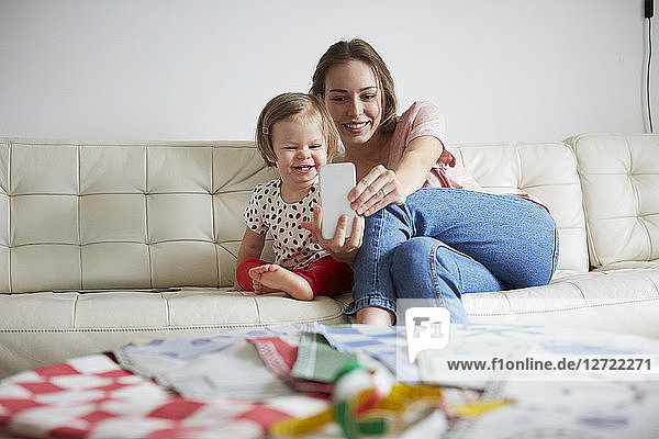 Smiling mother and daughter taking selfie through smart phone while sitting on sofa at home