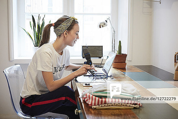 Podcaster using laptop while sitting on chair at home