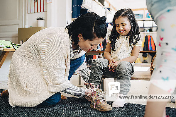 Side view of teacher helping happy girl wearing shoes in cloakroom at preschool