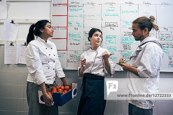 Chefs communicating against whiteboard in kitchen