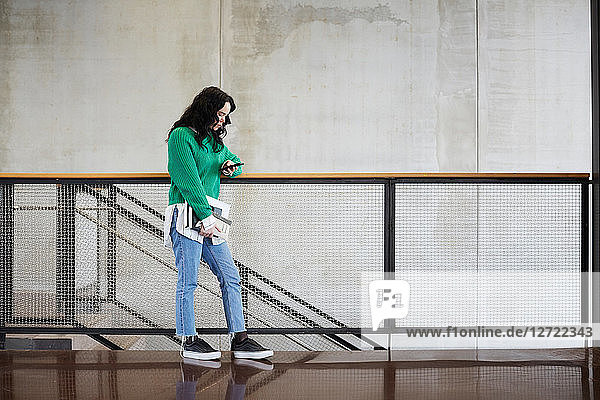 Young female student using mobile phone while standing at railing against wall in university