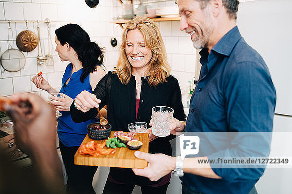 Smiling mature friends enjoying food and drinks in dinner party at home