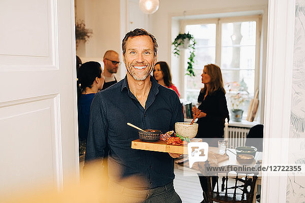 Portrait of smiling man with serving tray standing against friends in party at home
