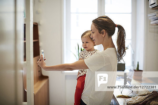 Female influencer taking selfie with daughter through smart phone at home