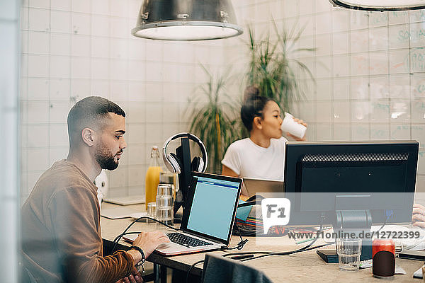 Young male hacker using laptop while female colleague sitting in creative office seen through window