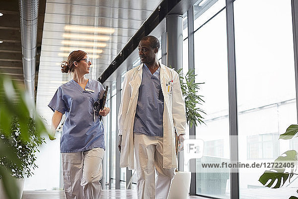 Confident female nurse discussing with male doctor while walking by window in corridor at hospital
