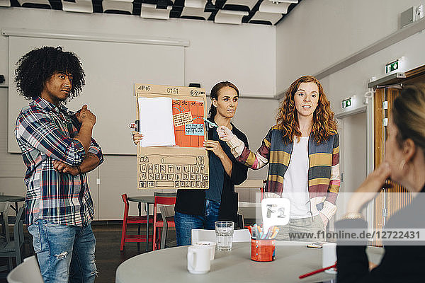 Confident businesswoman with colleagues explaining strategy to female manager at creative office
