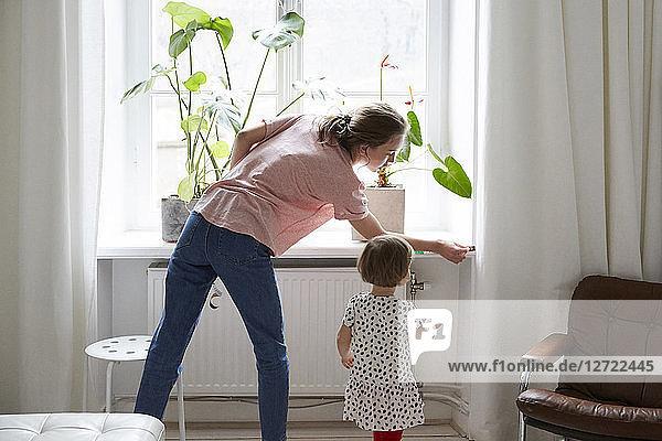 Daughter looking at designer measuring window at home