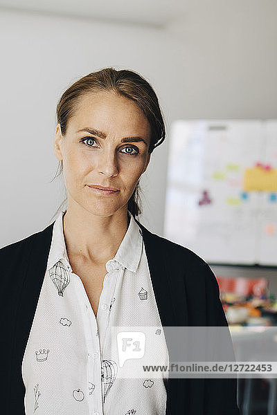 Portrait of confident mid adult businesswoman standing at creative office