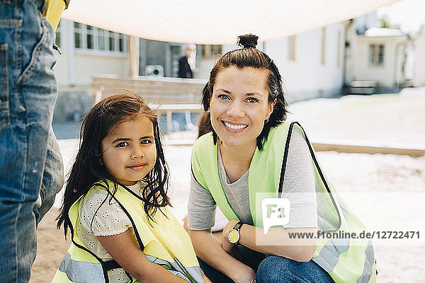 Portrait of smiling female teacher with student in playground against school building