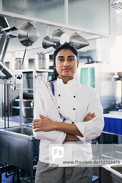 Portrait of female chef standing arms crossed in commercial kitchen