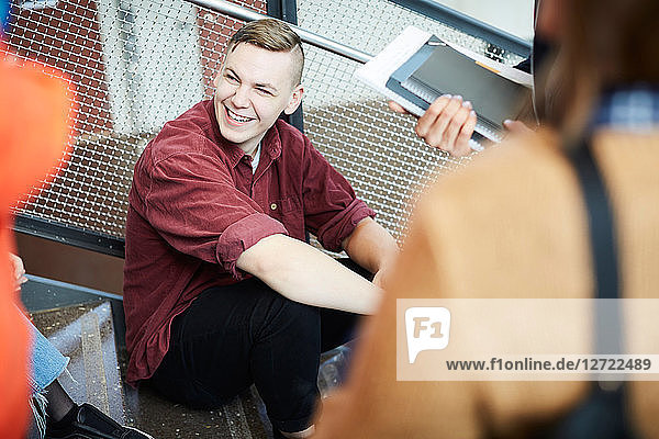 Smiling man sitting on steps while talking to friends in university