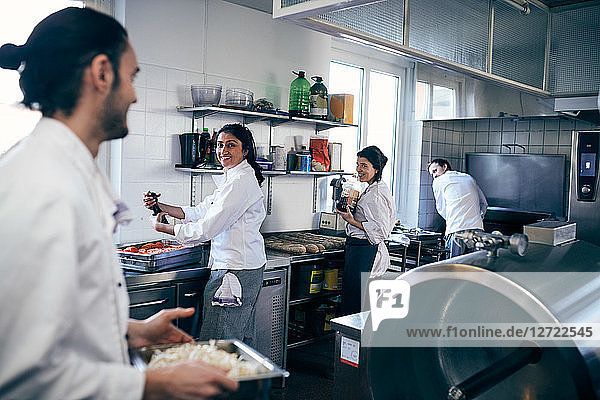 Happy chefs looking at colleague in commercial kitchen