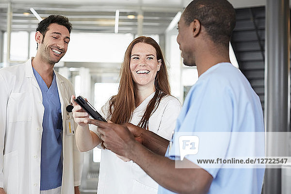 Smiling multi-ethnic healthcare workers discussing over digital tablet while standing in lobby at hospital