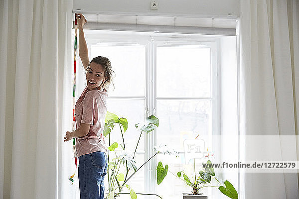 Smiling designer measuring window with tape measure at home