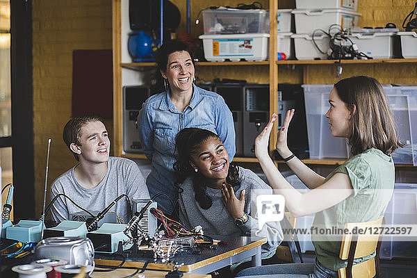Smiling female student gesturing while sitting with friends and teacher in classroom at high school