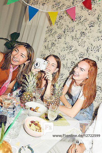 Tilt shot of young woman sitting with camera amidst multi-ethnic friends at dining table during party in apartment
