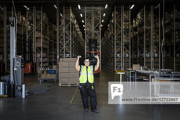 Full length of mature female warehouse worker gesturing while standing at storage room