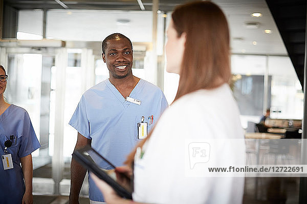 Mid adult nurses looking at young doctor standing at lobby in hospital