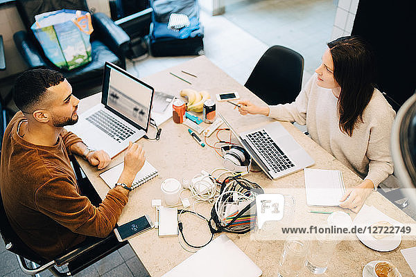 High angle view of male and female programmers discussing while sitting at desk in creative office