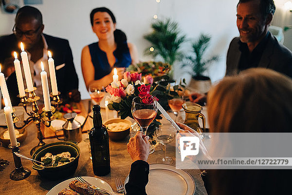 Woman raising toast with wineglass in dinner party at home