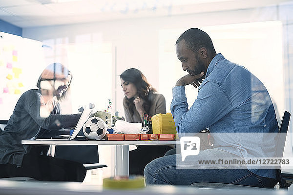 Male engineer thinking while colleagues working at table in office