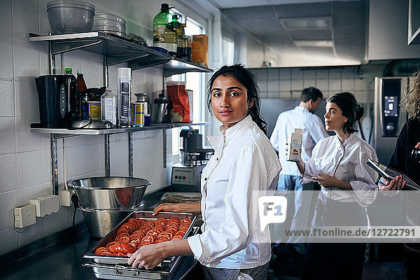 Portrait of chef with tomatoes in baking sheet at commercial kitchen