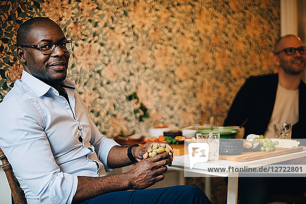 Portrait of man having food while sitting with friend by wall at home