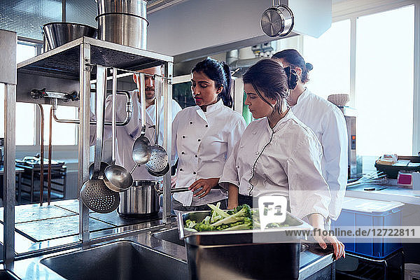 Chef team looking at colleague cooking food in commercial kitchen