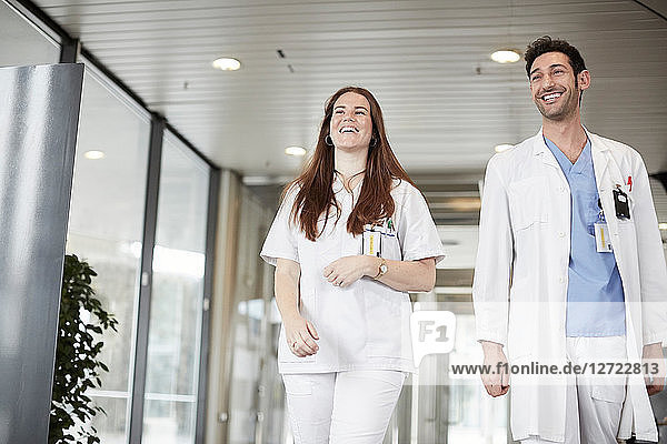 Smiling young healthcare workers looking away while walking in lobby at hospital
