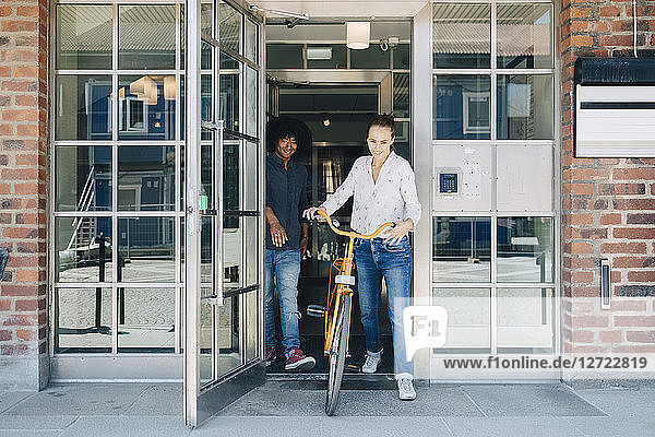 Full length of smiling businesswoman holding bicycle while walking with colleague through doorway at office