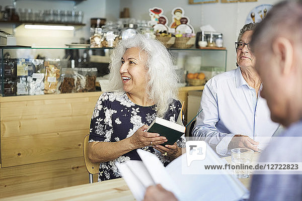 Senior man and woman with books sitting at table in coffee shop