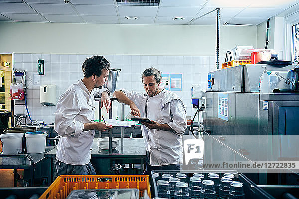 Male chefs with digital tablet and documents in kitchen
