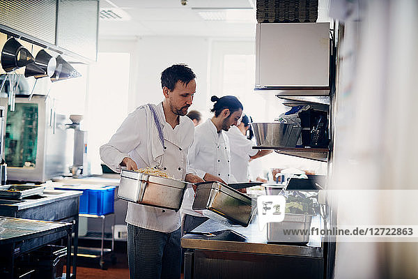 Young male chef carrying containers of food in commercial kitchen