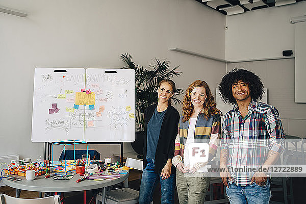 Portrait of smiling technician team standing by table and whiteboard at creative office