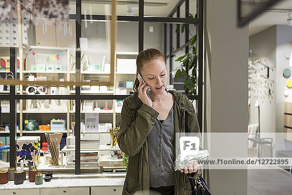 Young woman looking at box while talking through mobile phone at store