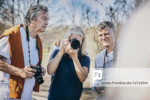 Senior woman using camera while standing with friends against bare trees at park