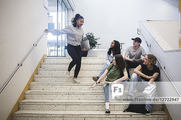 Smiling multi-ethnic students on staircase in high school