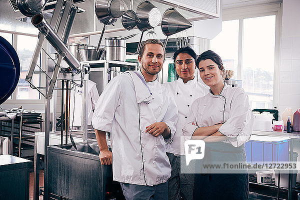 Portrait of multi-ethnic chefs standing in commercial kitchen