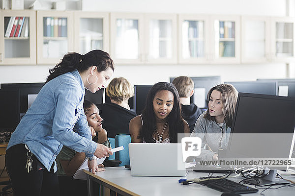 Mature teacher assisting female students using laptop in computer lab at high school
