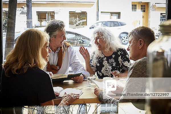 Male and female senior friends reading books while talking at table in coffee shop