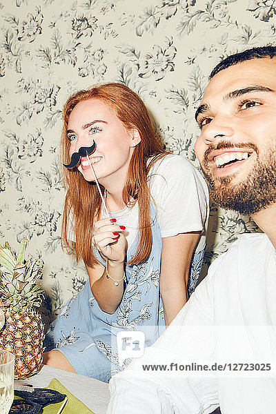 Smiling redhead woman holding mustache prop while sitting by male friend during party at home