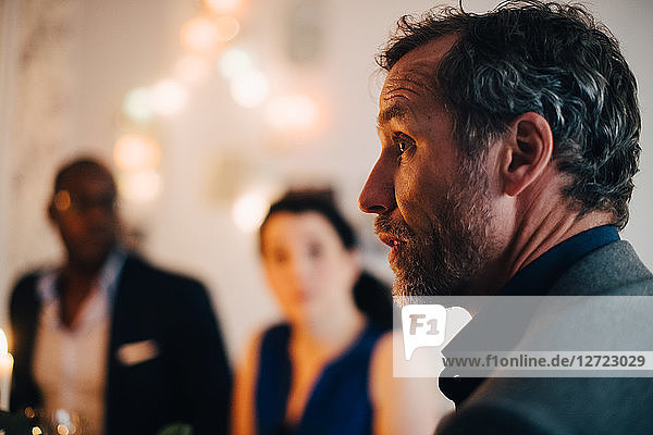 Close-up of mature man talking in dinner party with friends in background