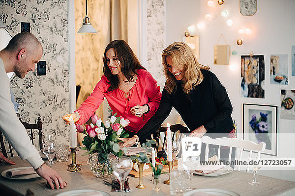 Mature male and female friends decorating dining table for party at home