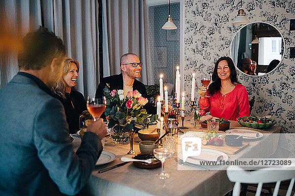 Mature male and female friends enjoying dinner party at home