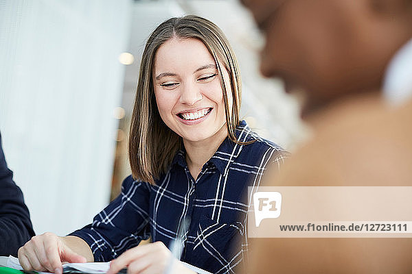 Smiling student studying with friend at table in university cafeteria