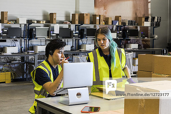 Confident young male customer service representative discussing with coworker over laptop while at desk in warehouse