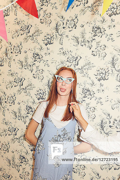 Cropped hand friend holding eyeglasses prop while smiling young woman sticking out tongue against wallpaper during party